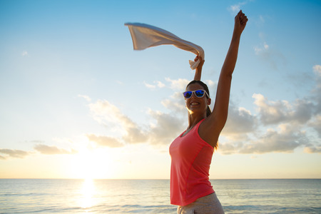 Fitness happy woman celebrating fitness workout success towards the sea and sunset at the beach. Training motivation and healthy lifestyle concept.