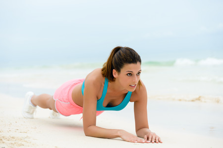 strength: Fitness woman doing plank isometric core exercise. Female athlete working out midsection on summer vacation at the beach.