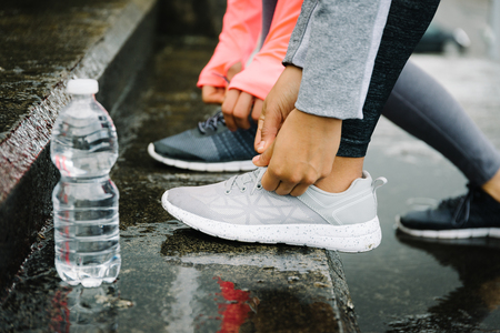 lacing sneakers: Urban running and fitness workout outdoor under the rain concept. Female athletes lacing sport shoes on wet stairs.