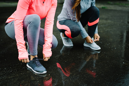 Urban athletes lacing sport footwear for running over asphalt under the rain. Two women getting ready for outdoor training and fitness exercising on cold winter weather. Foto de archivo