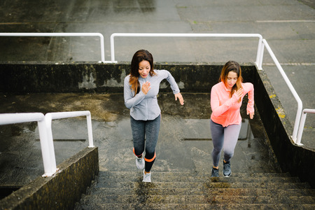 strength training: Urban fitness women running and climbing stairs for legs power and strength training. Female athletes working out outdoor in rainy winter day.