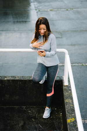 touched: Female athlete touched and happy by a smartphone message or email. Fitness woman using her cellphone.
