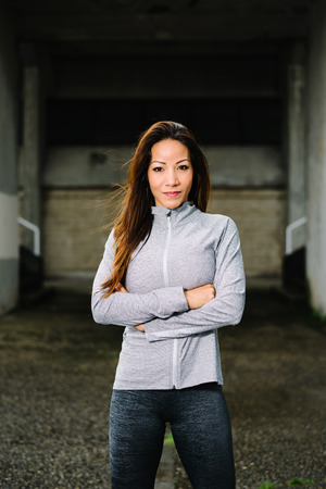 crossing arms: Female athlete portrait. Beautiful latin sporty woman crossing arms ready for urban fitness workout.
