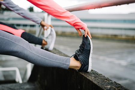 Dos atletas de sexo femenino que estira las piernas y hacer ejercicio. mujeres de la aptitud deportiva que hace ejercicio calientan antes de entrenar. Foto de archivo - 55458555