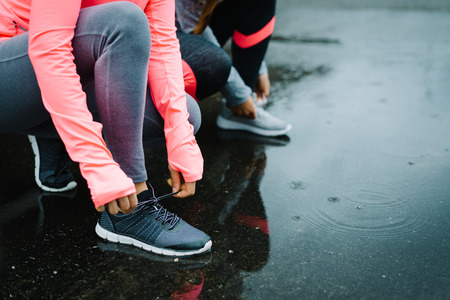 Urban athletes lacing sport footwear for running over asphalt under the rain. Two women getting ready for outdoor training and fitness exercising on cold winter weather. Фото со стока