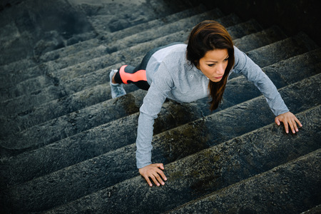 Urban fitness woman workout doing torso elevated push ups on urban stairs. Motivated strong female athlete training hard.