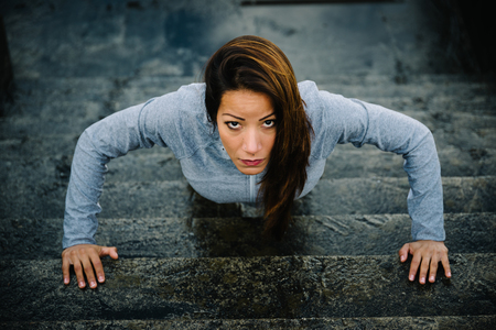 fitness training: Urban fitness woman workout doing torso elevated push ups on urban stairs. Motivated strong female athlete training hard.