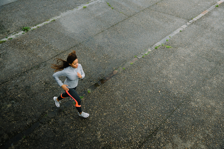 Top view of fit female athletes running on rainy day. Woman exercising outdoor on urban asphalt. Archivio Fotografico