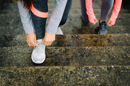 lacing sneakers: Urban running and fitness workout concept. Female athletes lacing sport shoes on wet stairs. Stock Photo