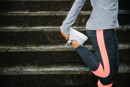 Urban träning och kör koncept. Kvinnan sträcker benen för att värma upp innan träningen och gå i trappor. Stockfoto