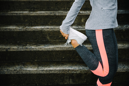 stairs: Urban workout and running concept. Woman stretching legs for warming up before exercising and climbing stairs.
