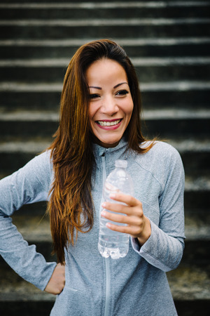spontaneous: Fitness female athlete spontaneous portrait. Relaxed sporty mixed race latin woman taking a workout rest for drinking water. Stock Photo