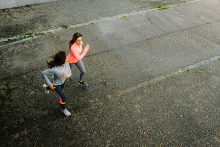 Top view of fitness female athletes running on rainy day. Women working out Friends training together and talking to each other.