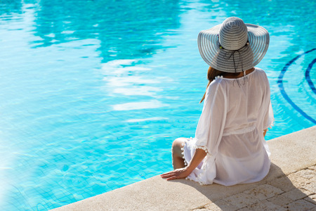 Back view of fashion woman on summer vacation relaxing at luxury resort spa poolside. Young  fashionable lady wearing sun hat and white kaftan.