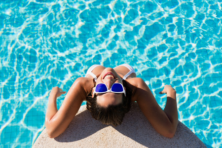 summertime: Top view of funny woman enjoying summer vacation in resort swimming pool. Beautiful brunette girl wearing sunglasses and having fun on summertime.