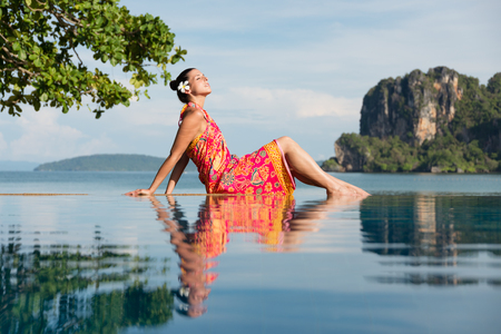 summer dress: Woman in traditional thai summer dress enjoying travel and relax in Krabi, Thailand. Beautiful girl relaxing at poolside towards the sea during asian travel. Stock Photo