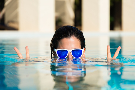 Summer fun and vacation concept. Playful woman doing success and victory gesture in swimming pool.