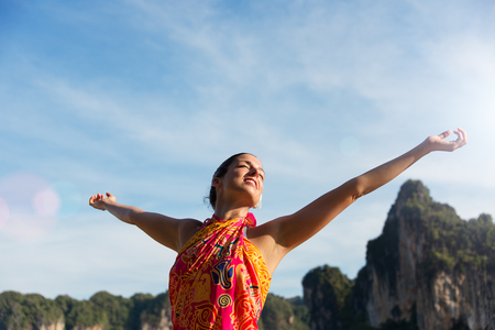 outstretching: Blissful woman relaxing and enjoying freedom on Thailand travel vacation in Krabi.