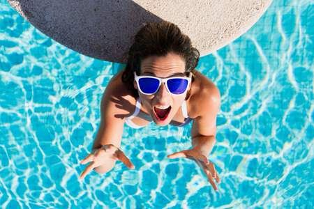 view girl: Top view of funny expressive woman gesturing enjoying summer vacation in resort swimming pool. Beautiful brunette girl wearing sunglasses and having fun on summertime.