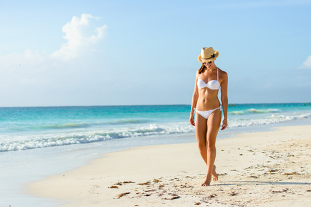 Relaxed woman in bikini enjoying tropical beach and caribbean summer vacation. Fit tanned brunette enjoying a walk by the sea at Playa Paraiso, Riviera Maya, Mexico.