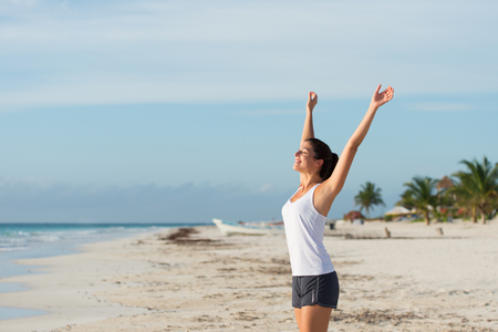 mayan riviera: Blissful sporty woman enjoying relax and tranquility after outdoor workout at caribbean beach. Healthy lifestyle on summer vacation concept.
