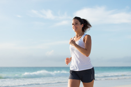 woman running: Sporty woman running at the beach by the sea on summer. Fitness and healthy lifestyle. Stock Photo