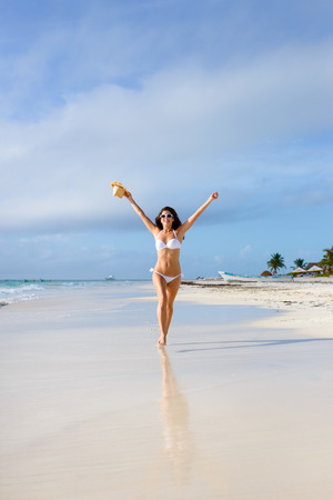 Beautiful happy woman in white bikini running free waving arms at tropical beach during caribbean summer vacation. Tanned brunette having fun by the sea at Playa Paraiso, Riviera Maya, Mexico. Stock Photo