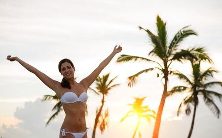 caribbean beach: Blissful woman enjoying freedom on relaxing sunrise at caribbean tropical beach. Caucasian brunette raising arms againts the sunset and palm trees. Riviera Maya, Mexico. Stock Photo