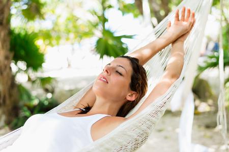 relajado: mujer relajada siesta en la hamaca. Relajante tranquilidad en vacaciones del Caribe.
