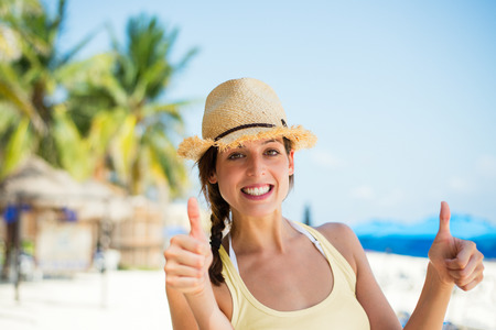 approving: Summer caribbean vacation travel. Successful happy woman doing thumbs up approving gesture at tropical beach. Playa del Carmen, Mexico. Stock Photo