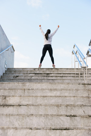 Successful athlete raising arms after running and climbing stairs. Urban fitness woman celebrating sport success and workout goal. Archivio Fotografico