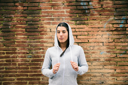 defiant: Defiant urban fitness woman portrait. City sport motivation. Female confident athlete outside in the street.