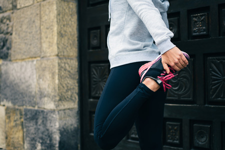 Running workout concept. Female athlete stretching for warming up before urban training.