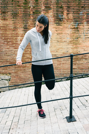 quadriceps: Female runner stretching legs and quadriceps muscle for warming up before running or fitness urban workout.