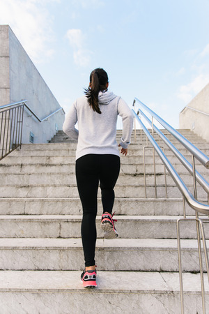 back view: Back view of sporty urban woman running and climbing stairs. Female athlete on hiit workout. Stock Photo