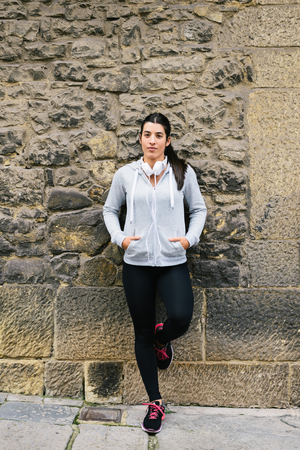 leaning: Female urban athlete leaning on a wall for resting after workout. Sporty fitness woman portrait.