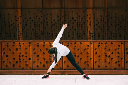 bend over: Young woman doing bend over twist fitness exercise for hamstrings and lower back workout. Female athlete warming up before urban training. Stock Photo