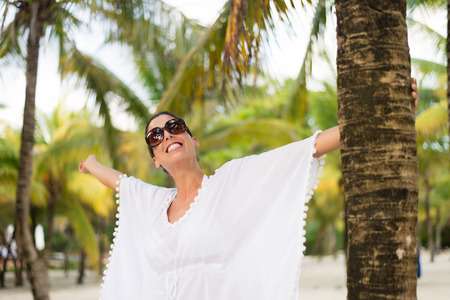 outstretching: Stylish fashionable woman enjoying and having fun on summer tropical vacation at beach. Female brunette wearing fashion white kaftan and sunglasses.