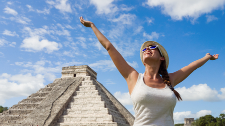 Happy woman enjoying travel tourism at Chichen Itza, Mayan Riviera, Mexico. Freedom and happiness on vacation. Фото со стока