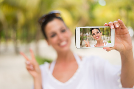 mayan riviera: Successful happy woman taking selfie photo with smartphone camera on tropical beach vacation. Female tourist having fun on travel to Mayan Riviera, Mexico. Stock Photo