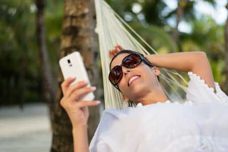 messaging: Happy young woman texting on smartphone while relaxing on a hammock at tropical beach. Brunette model enjoying summer caribbean vacation travel and relax. Stock Photo