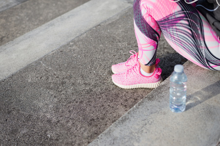 water sport: Urban running and fitness lifestyle concept. Pink female fashion sport shoes close up. Woman taking a workout rest.