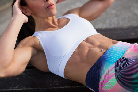 sit ups: Fit strong stomach abdominal muscles closeup. Fitness woman doing crunches exercise workout. Female fit athlete training midsection for  improve core strength.