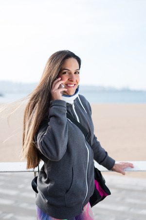 answering phone: Urban sporty woman answering phone call after workout. Stock Photo