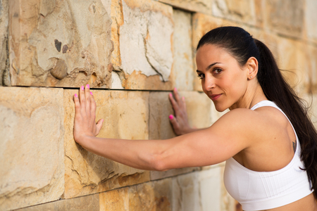 empujando: Female strong athlete pushing wall for stretching calves. Fit woman on urban workout looking confident at camera.