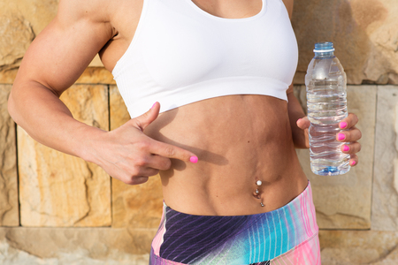 tight fit: Fitness workout for fat burning and slim down concept. Fit woman pointing her abs and tight midsection while holding a bottle of water. Stock Photo