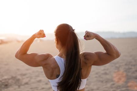 Fitness giovane donna flessione bicipite grande forti muscoli verso il sole in spiaggia urbana. Punto di vista posteriore della femmina armi culturista mostrando. Allenamento concetto di successo.