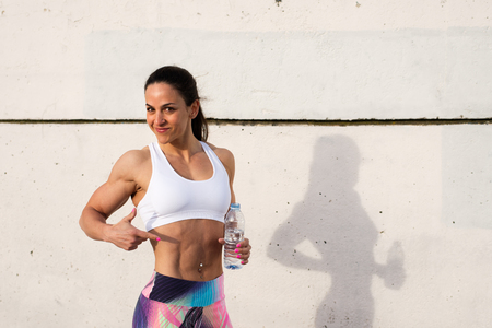 fat burning: Fit woman showing her fat burning workout success and taking a rest for drinking water. Female strong bodybuilder athlete after exercising. Stock Photo