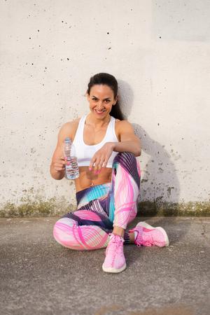 ropa deportiva: Ajuste a la mujer muscular de tomar un descanso del entrenamiento para el agua potable. Mujer atleta fuerte de descanso después de hacer ejercicio o correr. de deportes de la moda de primavera. Foto de archivo