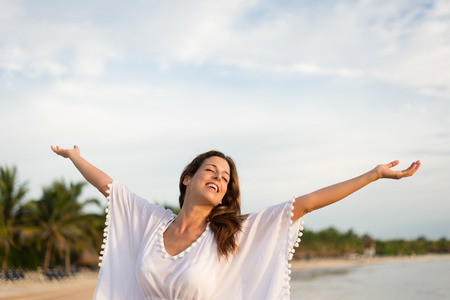woman sunset: Blissful woman at tropical beach enjoying relax, freedom and vacation.  Brunette female raising arms to the sky. Summer happiness and leisure.